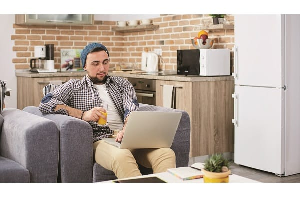 Portrait of serious fancy young man, student or freelancer businessman,works on his laptop at cozy modern home in loft style
